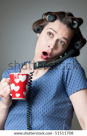 A woman in a domestic role gossiping on the phone with a mug. - stock photo