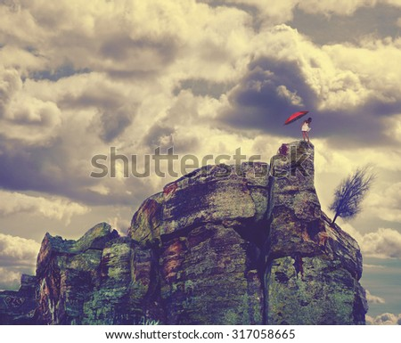 a woman in a dress and high heels standing on top of a cliff looking down holding an umbrella toned with a retro vintage instagram filter effect app or action - stock photo