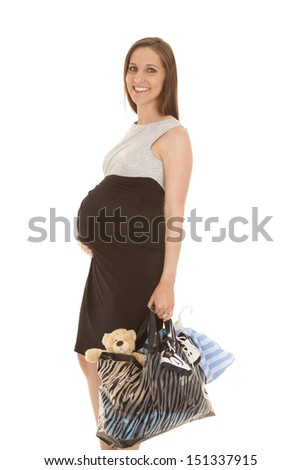 A woman in a dress pregnant holding a bag.