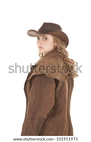 A woman in a duster is looking over her shoulder. - stock photo