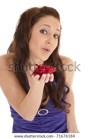 A woman in a fancy dress is blowing rose pedals. - stock photo