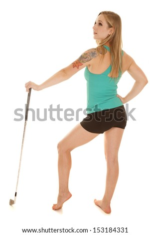 A woman in a green tank holding a golf club. - stock photo