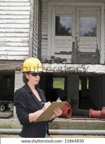 A woman in a hard hat in front of an old rundown house, writing something on a clipboard. - stock photo