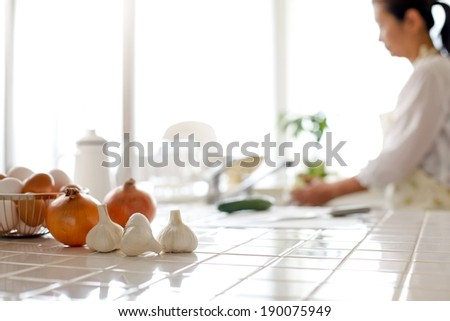 A woman in a kitchen washing vegetables behind onions and garlic. - stock photo