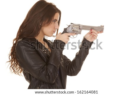 A woman in a leather jacket is pointing a gun. - stock photo