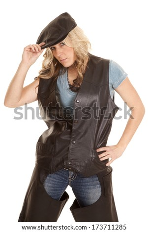 A woman in a leather vest and a hat with a serious expression on her face.