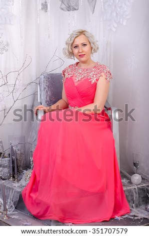 A woman in a long pink dress sitting on a chair like a snow queen - stock photo