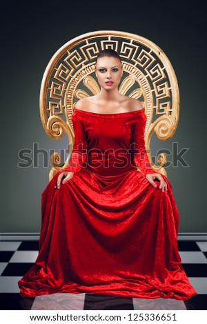 A woman in a luxurious red dress sitting on a golden throne - stock photo