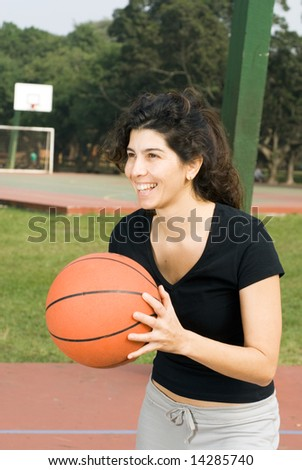 A woman in a park, in front of a basketball court, passing a basketball. - vertically framed - stock photo