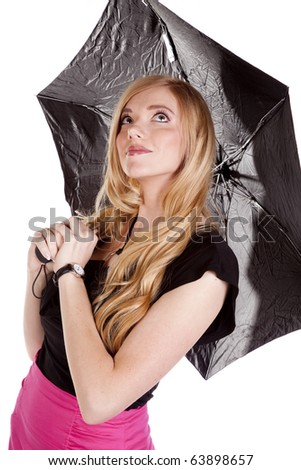 A woman in a pink skirt is holding an umbrella and looking up. - stock photo