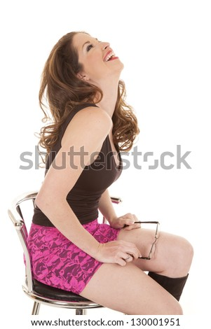 A woman in a pink skirt is holding her glasses in her hand. - stock photo