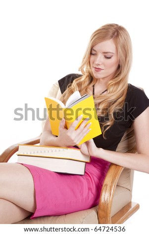A woman in a pink skirt is reading a yellow book.