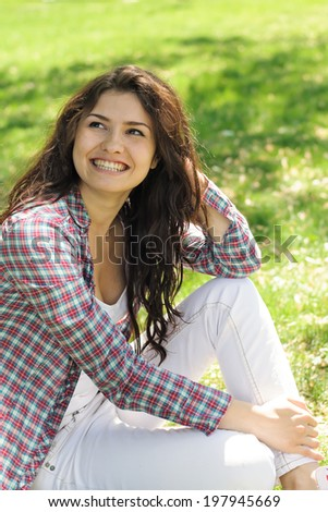 A woman in a plaid shirt sitting on the green grass