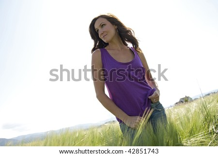 A woman in a purple shirt in a green field. - stock photo