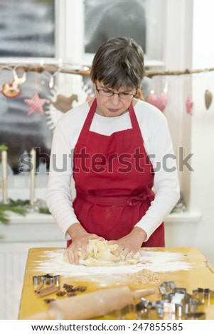 a woman in a red apron baking christmas cookies in her kitchen