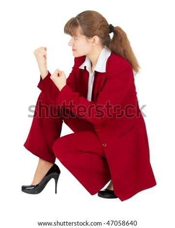 A woman in a red business suit sitting in a combat stance