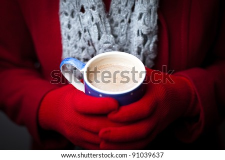A woman in a red coat and gloves warms her hands on a mug of hot chocolate.  Focus on the drink. - stock photo
