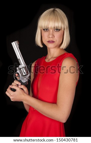 A woman in a red dress holding a revolver. - stock photo