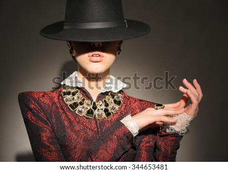 A woman in a red jacket with jewels - stock photo