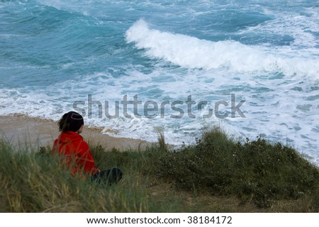 A woman in a red top sits on top of a sand dune looking out over the ocean