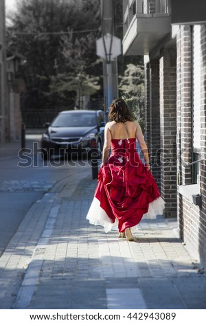 A woman in a red wedding dress, walking down a street. A concept of a wedding, or the exact opposite: a runaway bride.  - stock photo