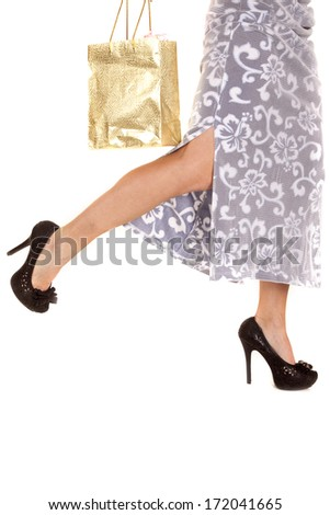 A woman in a skirt legs only with a shopping bag. - stock photo