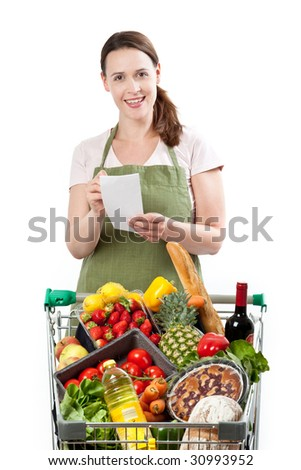 A woman in a store assistant role with a list on a white background and a cart full of fresh goods. - stock photo