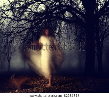 a woman in a very foggy forest - stock photo