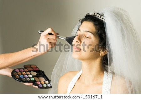 A woman in a wedding dress, sits patiently, getting her make-up done. - horizontally framed - stock photo