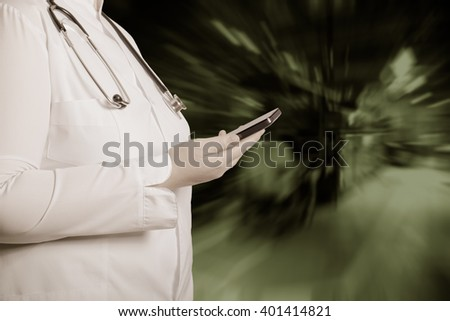 A woman in a white uniform robe with electronic device in her hands in front of a blurred background. Toned.