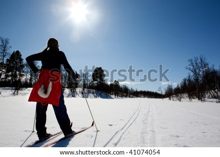 A woman in a winter landscape cross country skiing