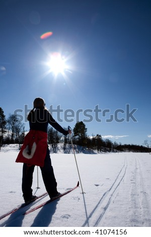 A woman in a winter landscape cross country skiing - stock photo