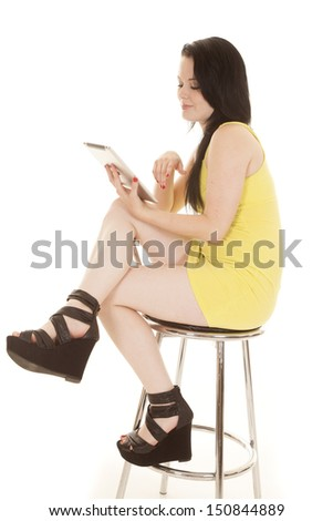A woman in a yellow dress and heels with a tablet.