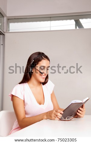 A woman in an office talking on the phone in a business call - stock photo