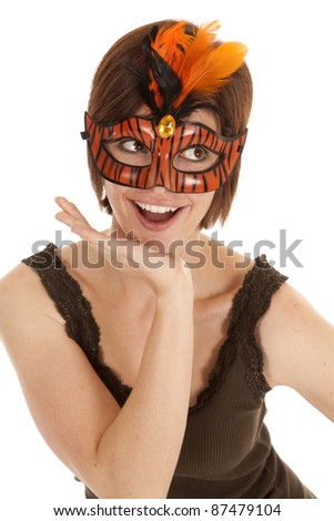 A woman in an orange mask with feathers with a smile on her face. - stock photo
