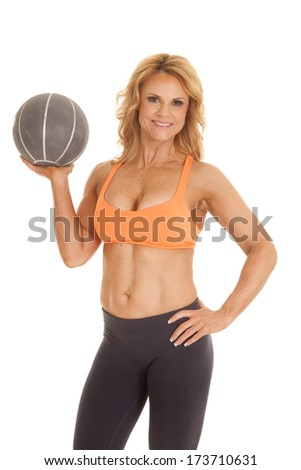 A woman in an orange sports bra holding a medicine ball.