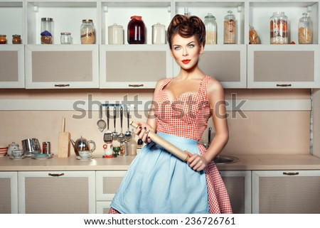 A woman in apron with rolling pin in hand in the kitchen. - stock photo