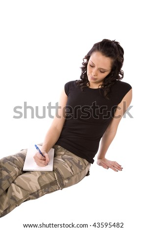 A woman in army clothes writing a letter home with a sad expression on her face.