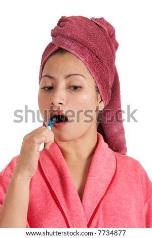 A woman in bathrobe brushing her teeth