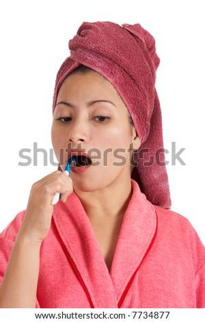 A woman in bathrobe brushing her teeth - stock photo