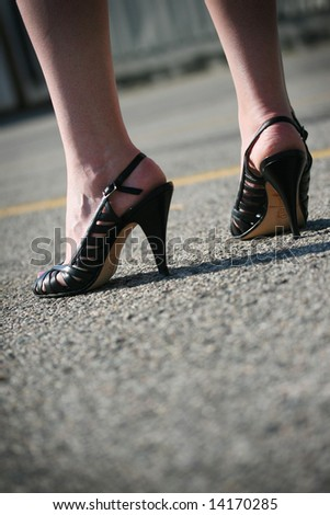 A woman in black heels standing in a parking lot