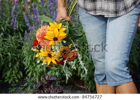 A woman in denim jeans holding a colorful bouquet of flowers. - stock photo