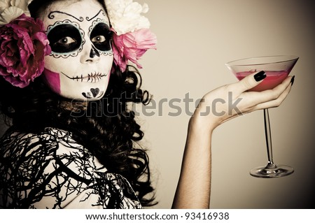 A woman in Halloween costume Holding a Glass With Red Liquid - stock photo