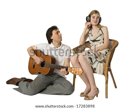 A woman in headphones and a man playing guitar for her - stock photo