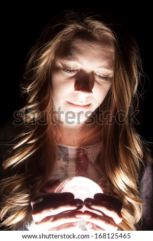 A woman in her American flag shirt holding on to her lighted crystal ball. - stock photo