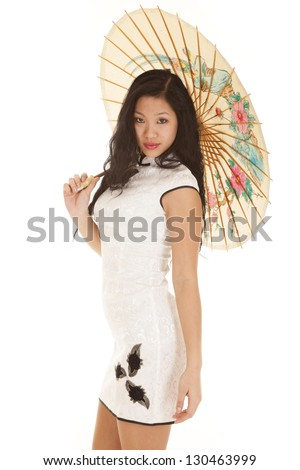 a woman in her Asian dress holding on to an paper umbrella. - stock photo