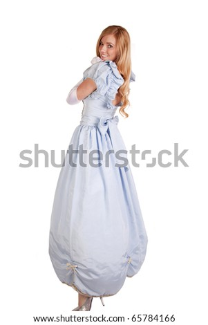 A woman in her beautiful blue princess dress looking over her shoulder with a smile on her face. - stock photo