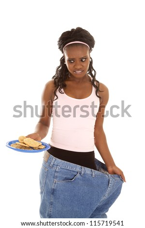 a woman in her big pants looking down at a plate of cookies with a funny expression.
