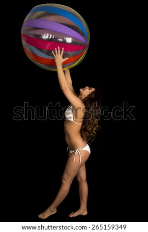 a woman in her bikini holding up her beach ball, laughing. - stock photo