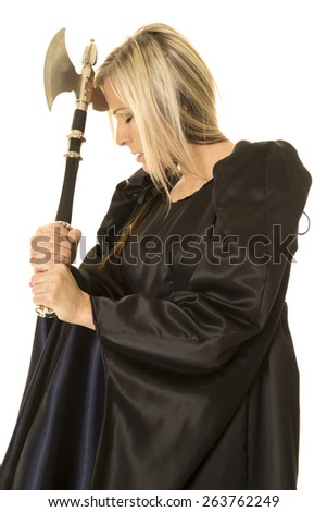 A woman in her black and blue medieval dress with a hatchet by her head, she looks frustrated. - stock photo